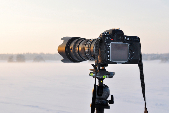 Digital SLR camera on a tripod shooting a sunset in a snowy landscape